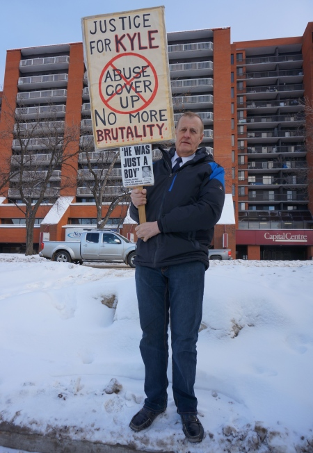 Rob Wells with Protest Sign [photo taken by author on 6 January 2014]