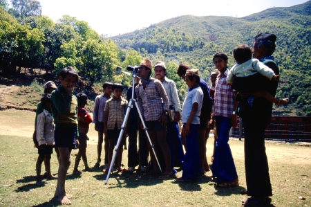 Locals line up to see what Lig Lig Mountain looks like through a camera's telephone lens.
