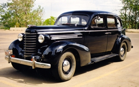 The 1937 Oldsmobile [assembled in Regina, Saskatchewan, incidentally]. This photo was taken before Mr. Rust attacked the wheel wells. Now there's a guy people should put a contract on.