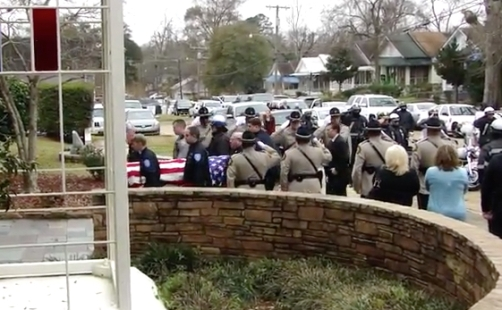Carl Bordelon's flag-draped casket is carried into the church by police officers after passing a row of saluting police.