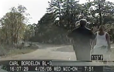 Officer Carl Bordelon talking to 'jogger' Richard McNair on railroad tracks near Ball, Louisiana.