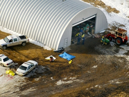 The tarped-over bodies of the four dead Mounties. One is to the rear of the police cruiser [note passenger side window shot out]; two appear to be under the blue tarp and the fourth under a yellow tarp just inside the quonset hut. Photo by Rick MacWilliam of the Edmonton Journal.