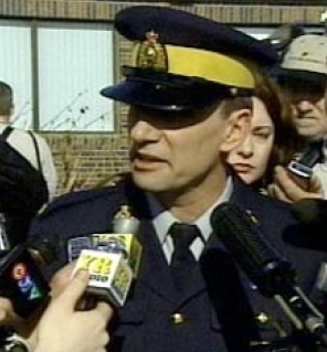 Corporal Oakes being peppered by questions from reporters outside the RCMP building in Mayerthorpe.