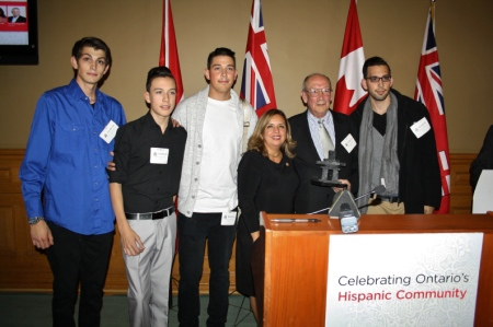 Pastor Valle-Garay receiving an award from the Province of Ontario. He is with his four sons.